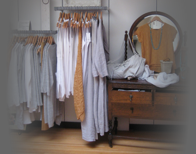 Grey, White and Tan clothes hanging on racks in store